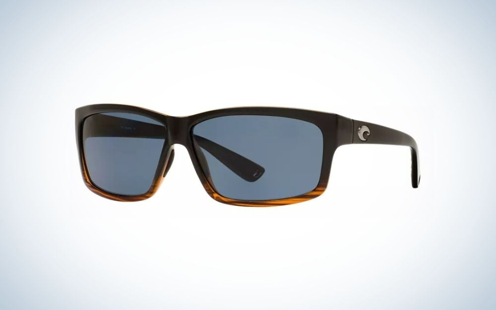 A pair of sunglasses with a black and brown frame and structure and two lenses in light translucent blue.