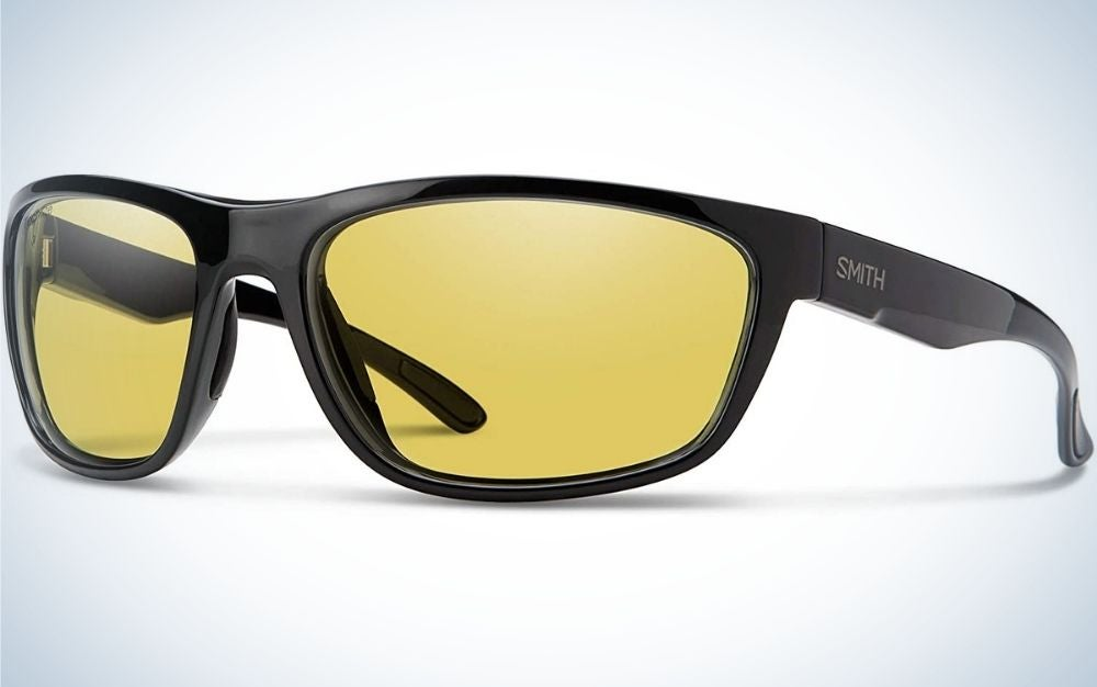 A pair of sunglasses with a black frame and structure and two lenses in bright neon yellow.