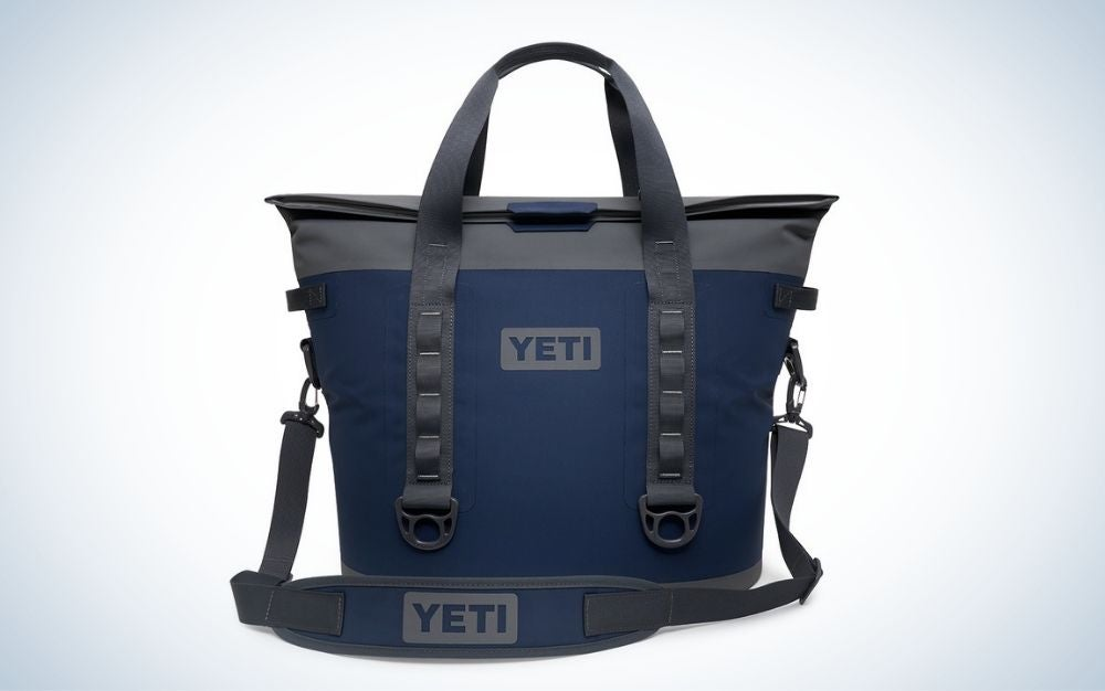A blue shoulder bag with a black holder and the brand name on it.