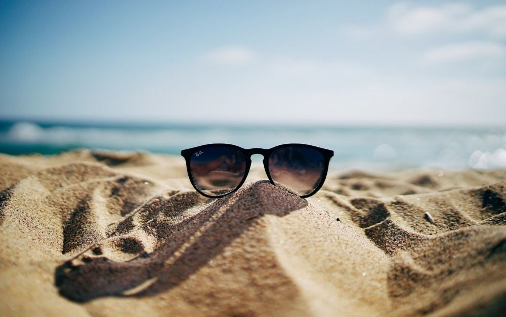 A pair of Ray Ban black sunglasses laying into the sand of the sea.