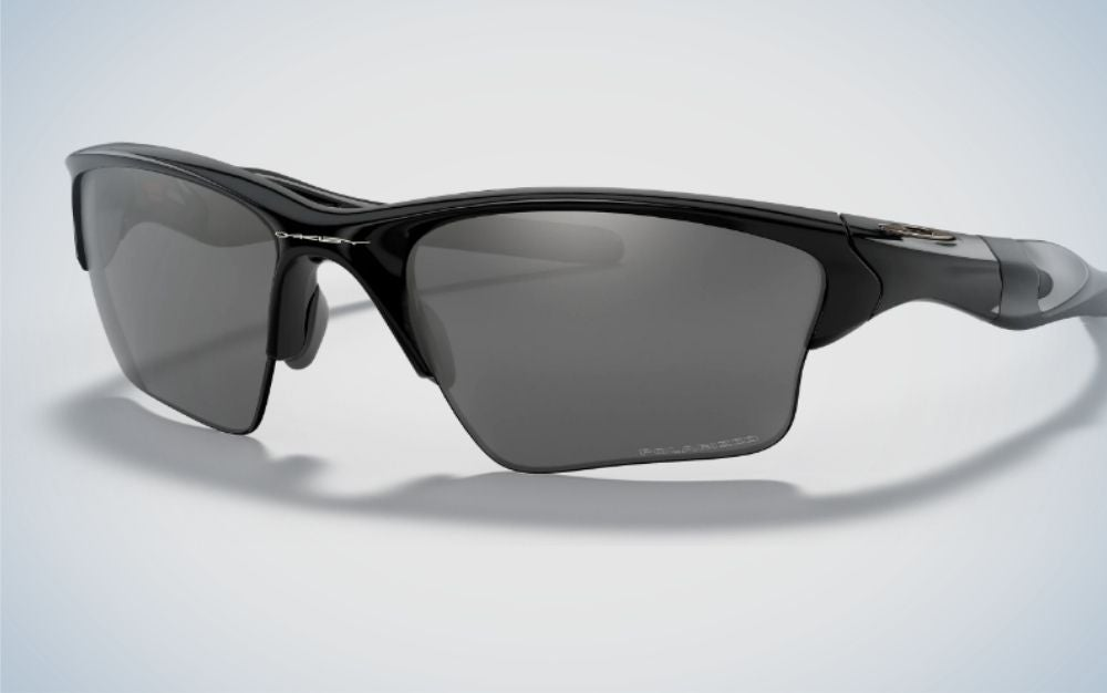 A pair of sportive glasses with a black skeleton structure and also light black lenses with name f brand into the skeleton.