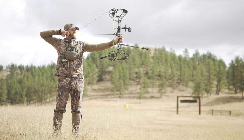 Guy shooting bow at target