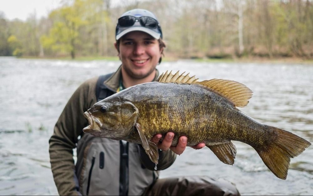 Man holding a big fish in front of a river