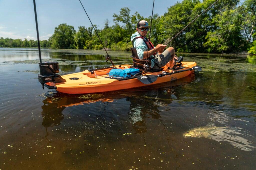 Fisherman on an orange Hobie Mirage Outback kayak reeling in a largemouth bass.
