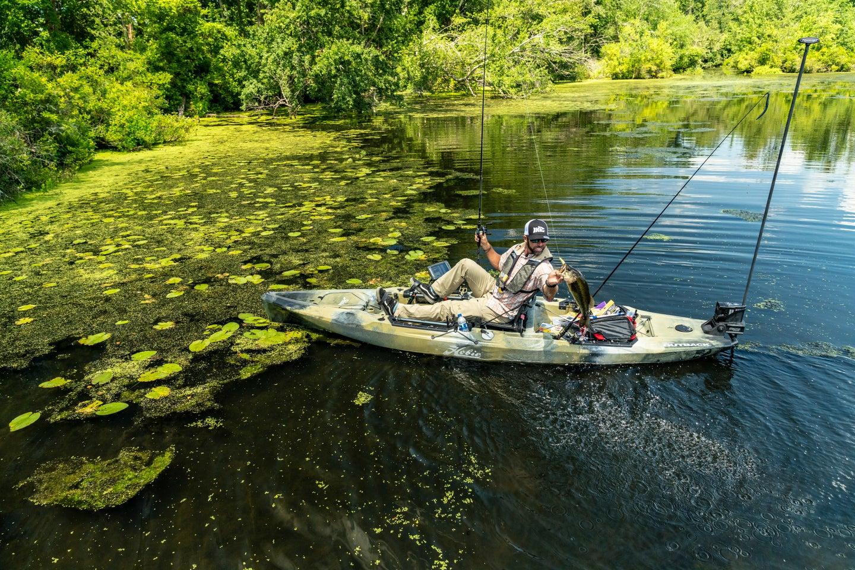 Fisherman hold bass on a Hobie fishing kayak