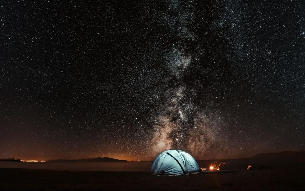 Camping tent next to a fire under the sky full of stars