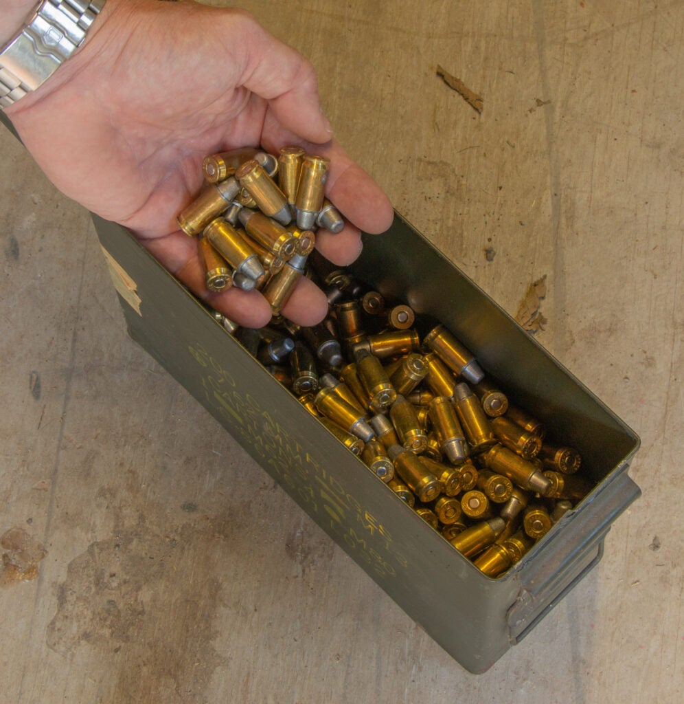 A handfull of ammo being pulled from an ammo can.