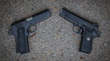 Two model 1911 handguns on a concrete slab.