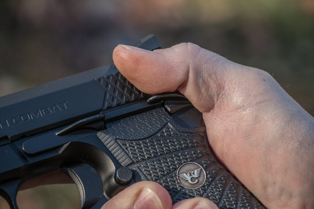 Thumb engaging with a safety on a 1911 pistol.
