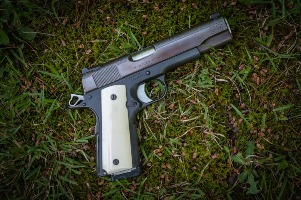 A custom handgun sitting on the grass.
