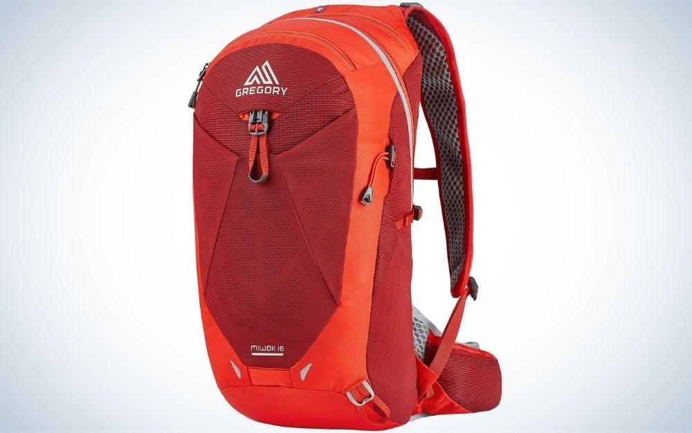 A backpack with a bright orange color and a large pocket with a zipper in front of it.