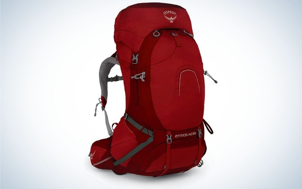 A backpack with a bright cherry color and with gray arms from the back and a large pocket with a zipper in front of it.