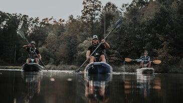 Three kayakers paddling
