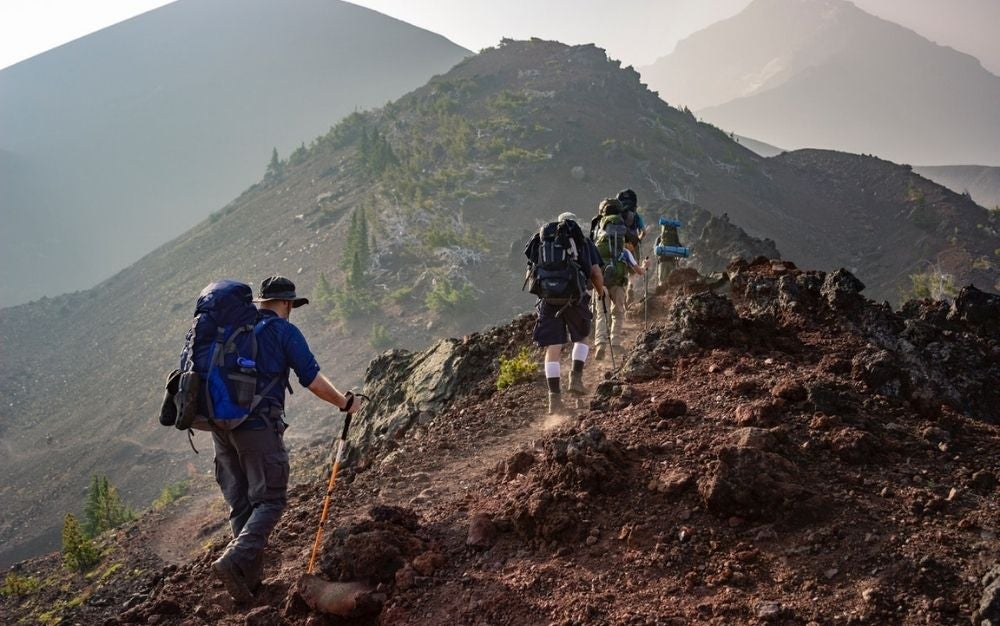 Group of people walking and hiking into the mountains with backpacks in their shoulders.