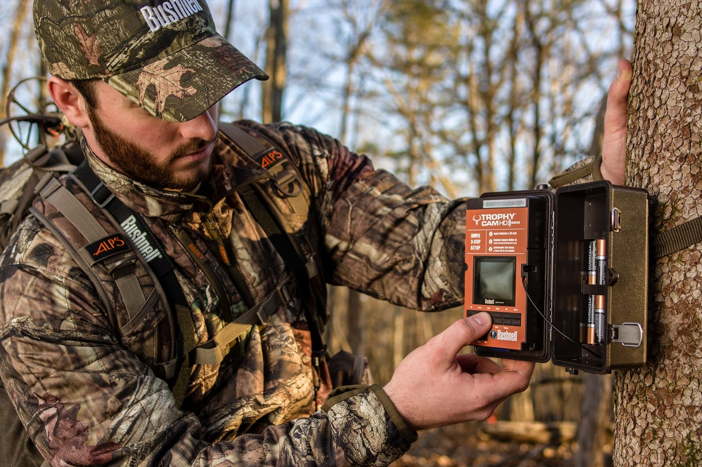 A deer hunter shows where to mount a trail camera