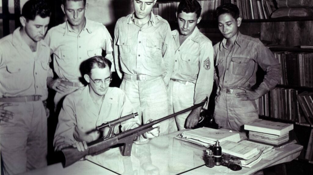 group of soldiers examining a prototype rifle.