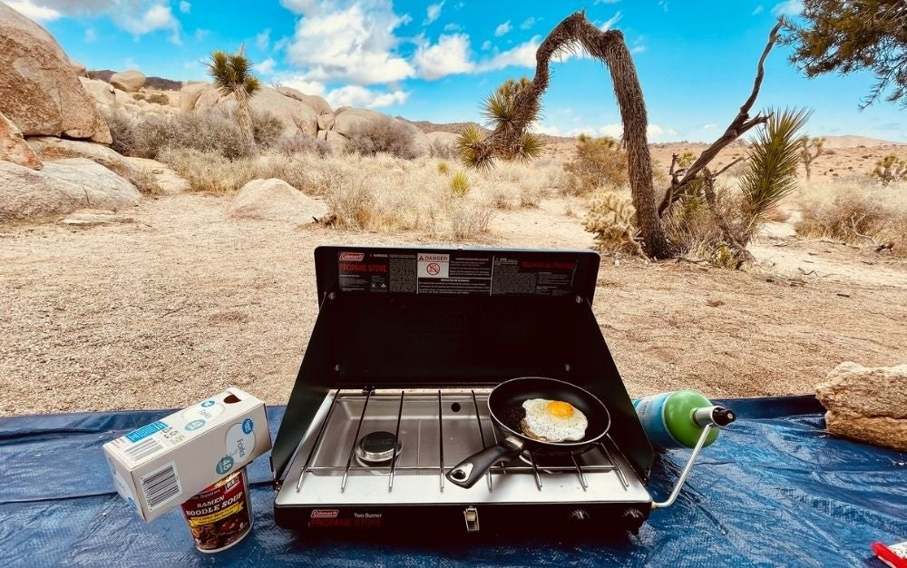 A propane camping stove in use.