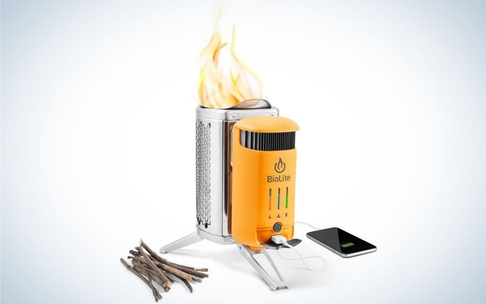 BioLite CampStove 2+ with a bundle of sticks to the left and a phone to the right