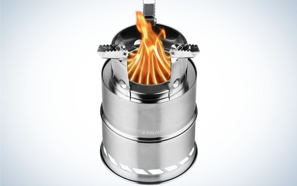 A silver-colored camping stove in the shape of several cylinders of different sizes on top of each other and a flame container that stands in the center of the stove.