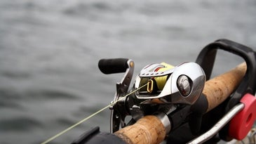 A fish hook and a silver spinning reel photographed up close in the middle of a water space.