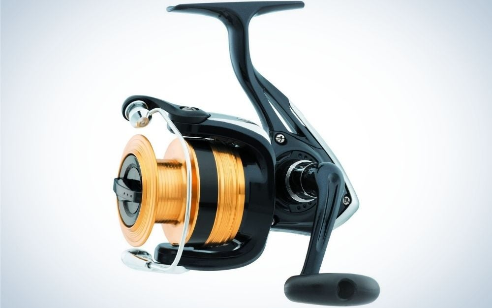 A spincast reel at the beginning of its body is gold-colored with narrow circles compared to the whole machine and in its tail a propeller from above and one side is black.