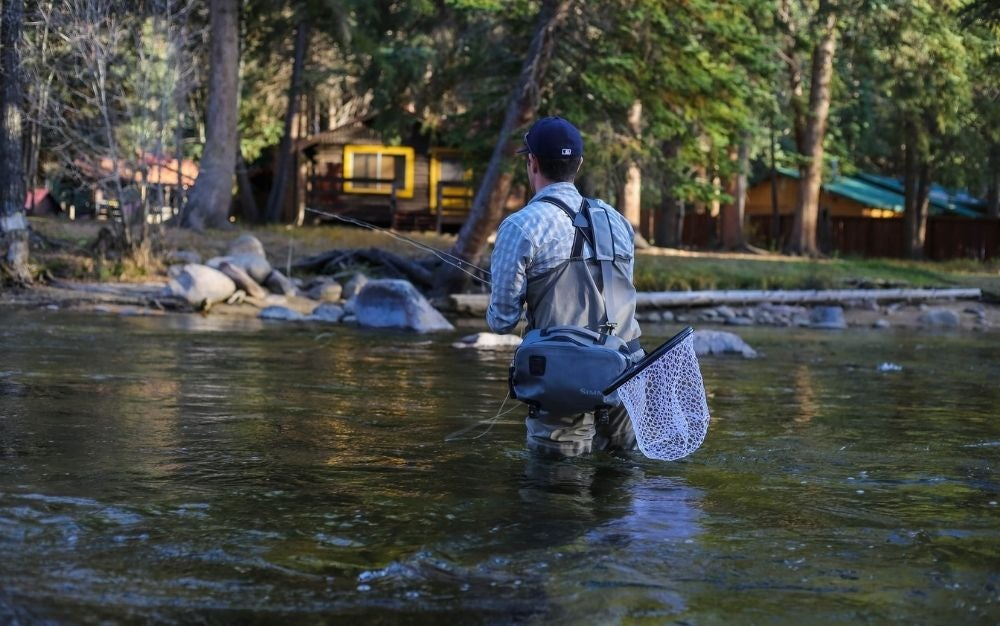 A man fishing with trout fly rods, in the middle of the water in front of some wooden houses and some big trees.