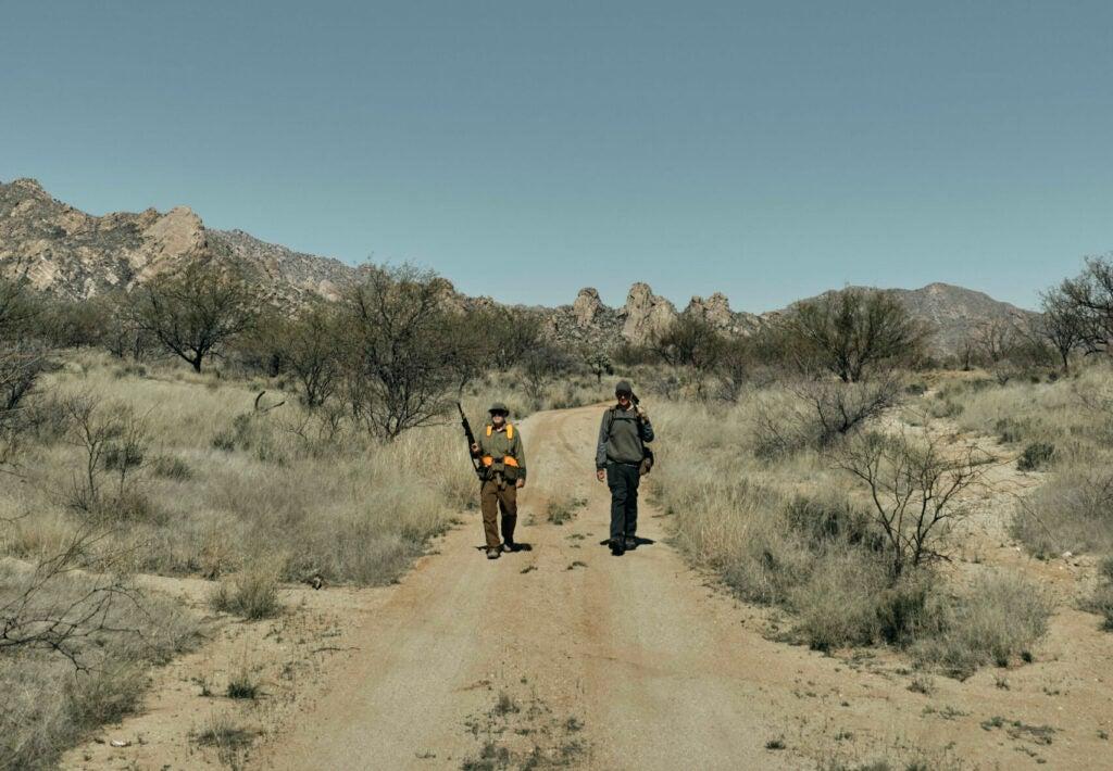 hunters walking a dirt road in Arizona.