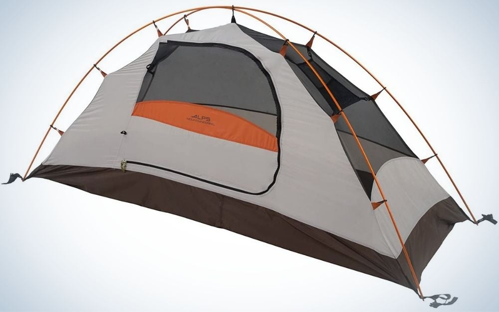 A green camping tent with orange and blue parts in it, as well as two ropes that are attached to the orange tent from above.