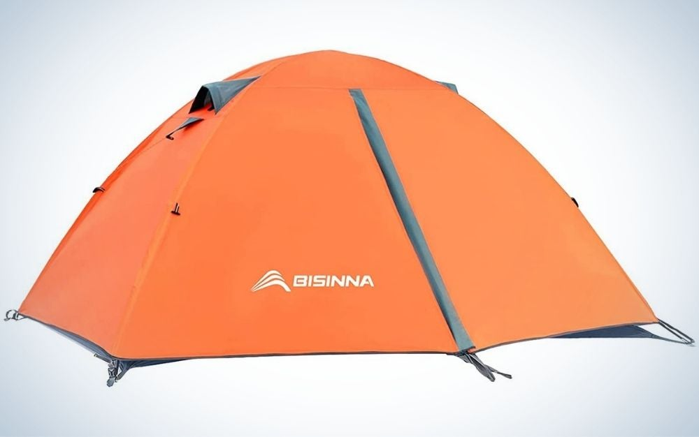 A small camping tent with an oval shape which is all orange with some small blue markings.