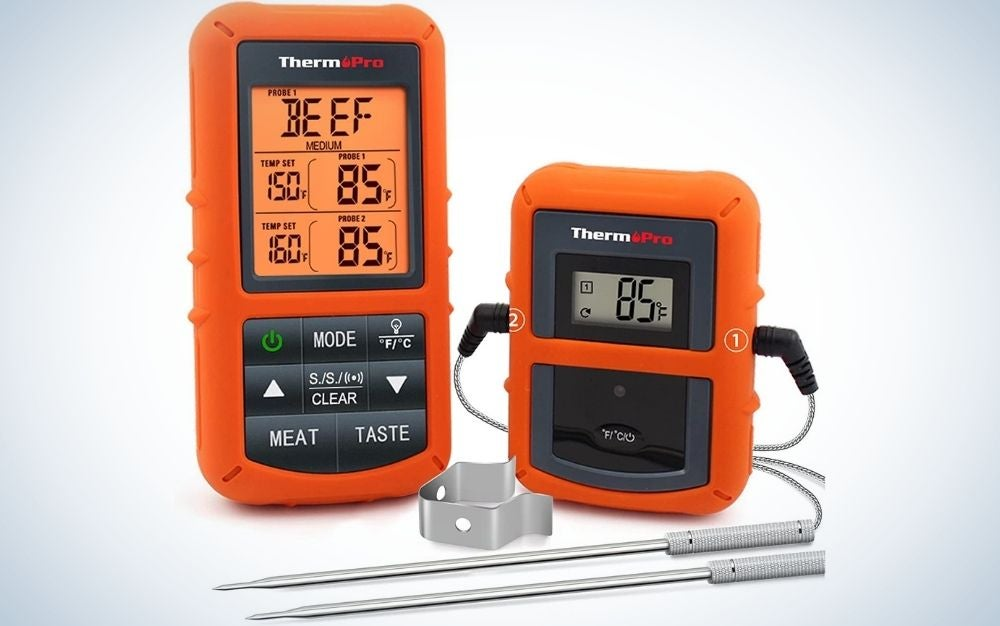 Two orange appliances with some buttons and indicator numbers on them, as well as two silver sticks connected to these temperature gauges for the meat.