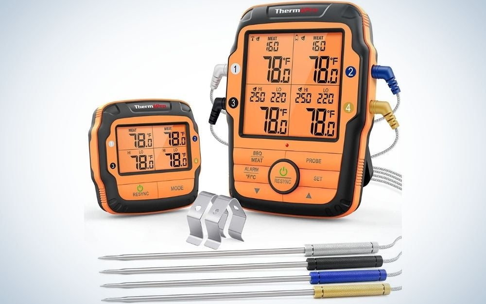 Two orange appliances with some buttons and indicator numbers on them, as well as four sticks with four colours connected to these temperature gauges for the meat.