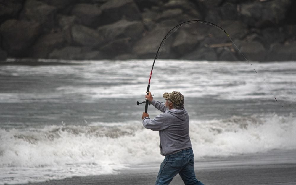 A man in a shirt and hat who is on the seashore and has a fishing rod in his hand.