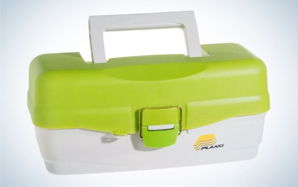 A plastic box in the shape of a small square suitcase in light green and white, as well as a holder on top of it.