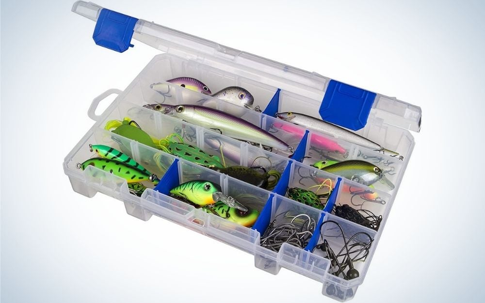A transparent plastic box with some blue parts, which is open and inside it several different baits for catching fish.