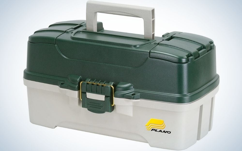 A plastic box in the shape of a small square suitcase in green and beige, as well as a holder on top of it.