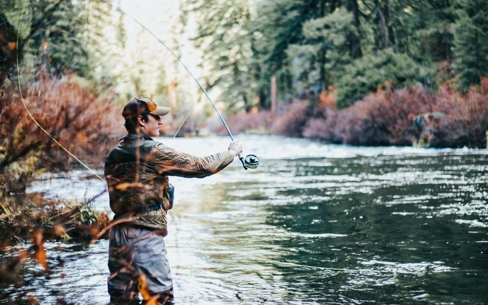 Person using a trout fly reel on the river
