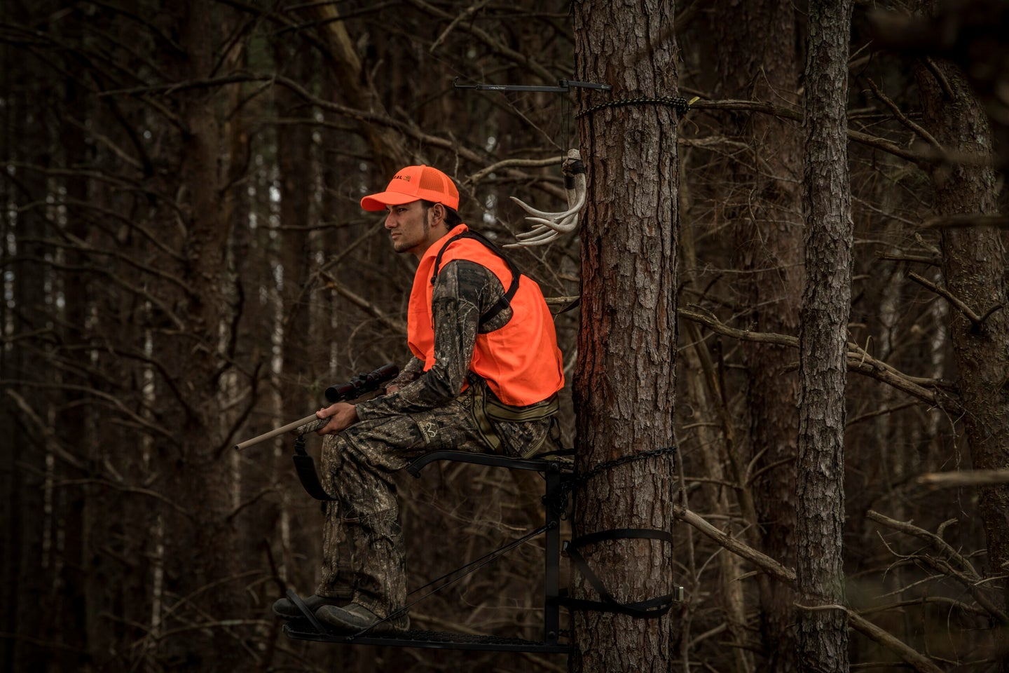 rifle hunter sitting in a tree stand