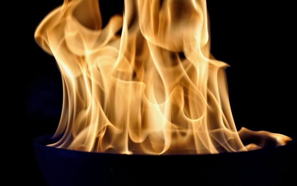 A strong flame into a darken background.