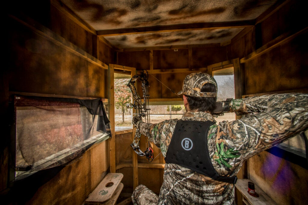 Bowhunter shoots a compound bow in a blind
