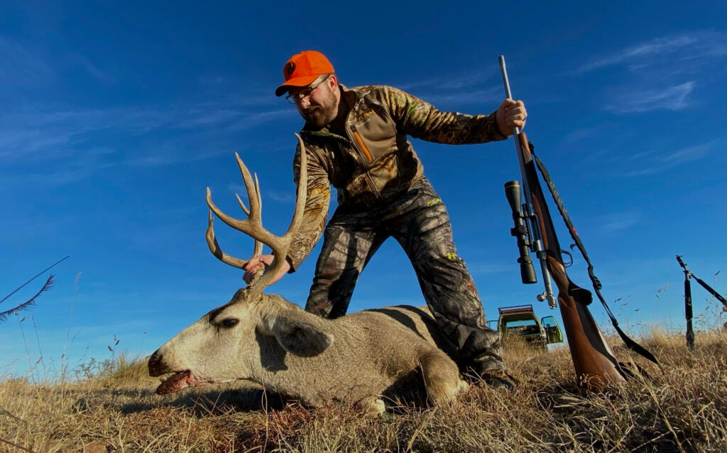 Hunter with mule deer buck