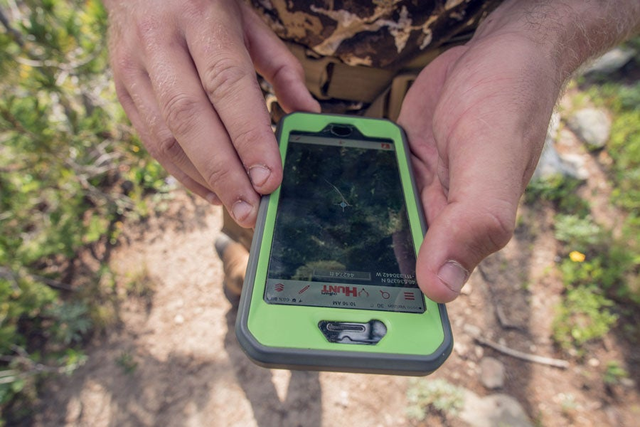 Hunter looking at digital map of public land information on phone