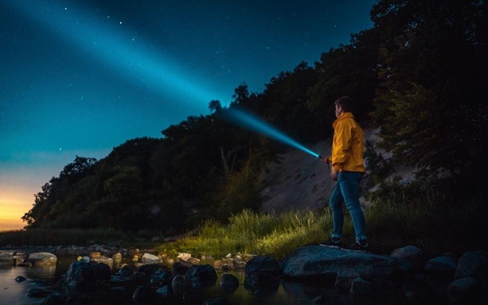 Person holding flashlight towards the sky
