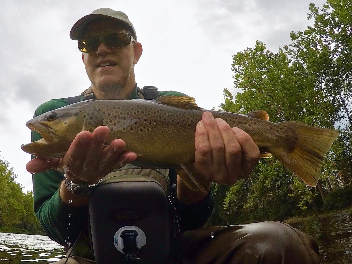 man holding a brown trout.