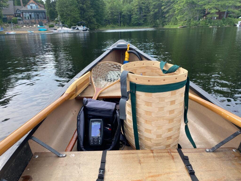 A canoe with a Garmin Striker 4 inside, sitting on a lake.