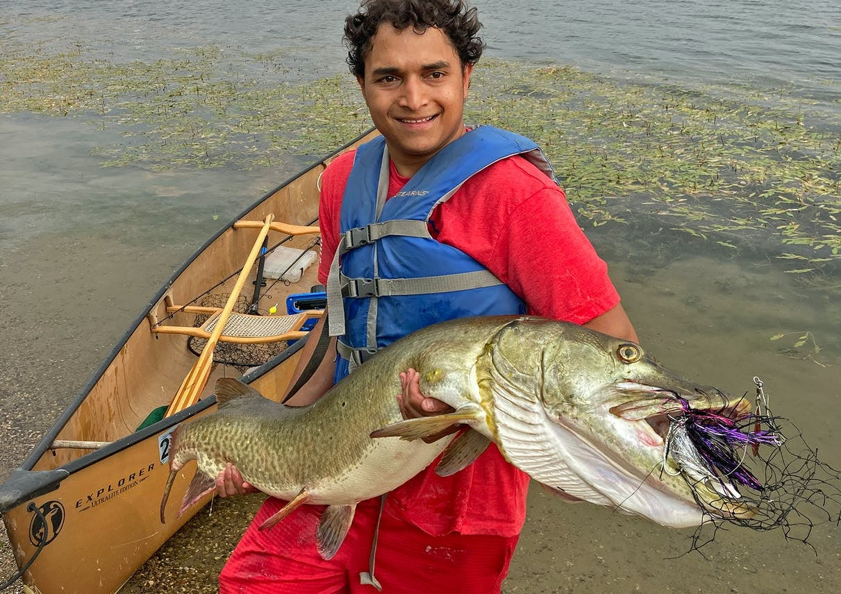 young man with curly black hair holding big muskie in front of canoe
