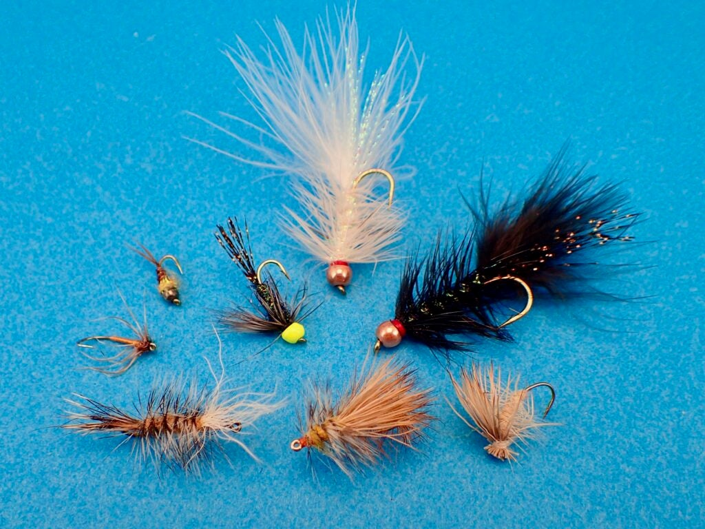 Collection of fishing flies on a blue background.