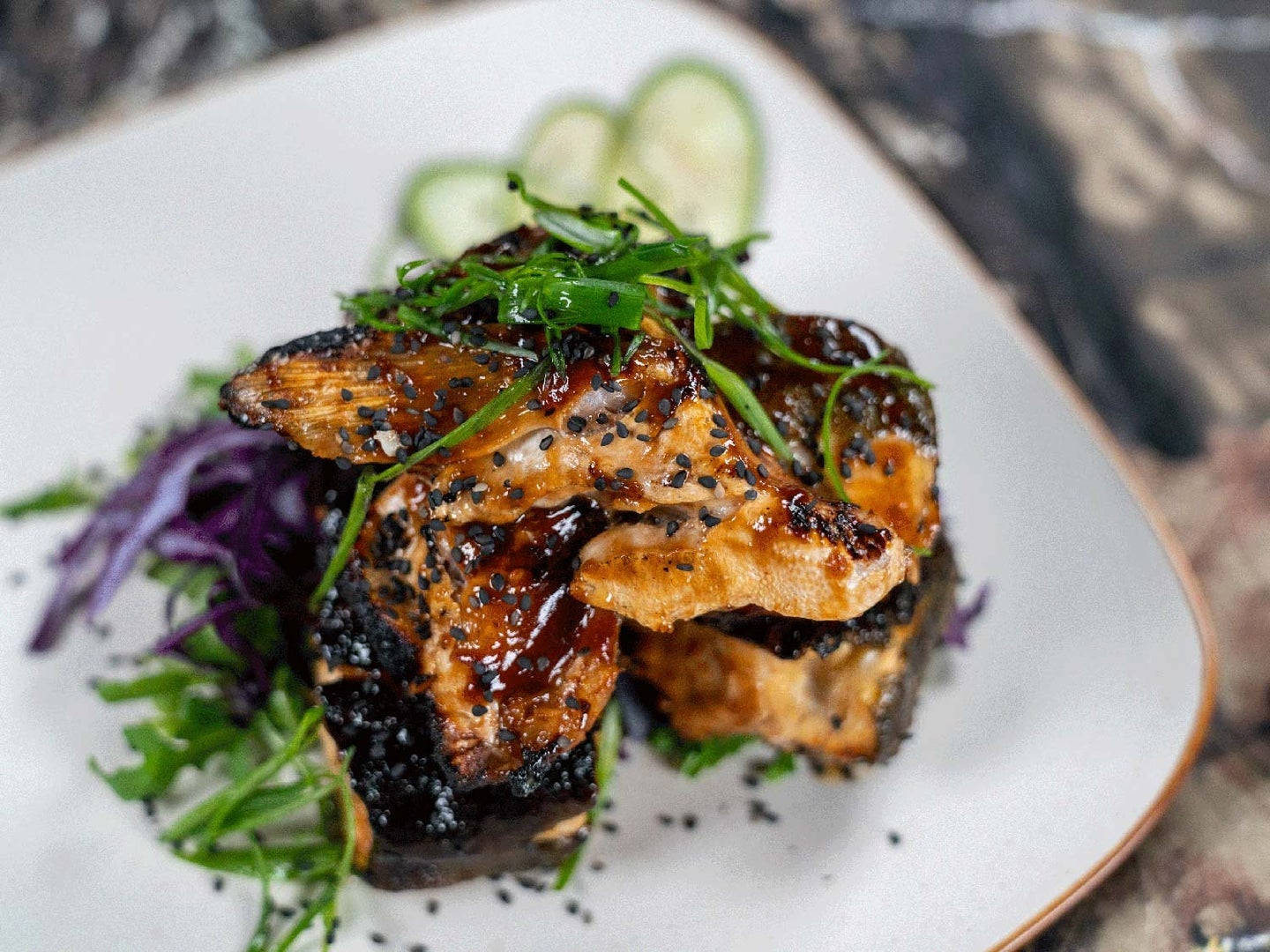 Marinated and grilled trout collars on a bed of greens.