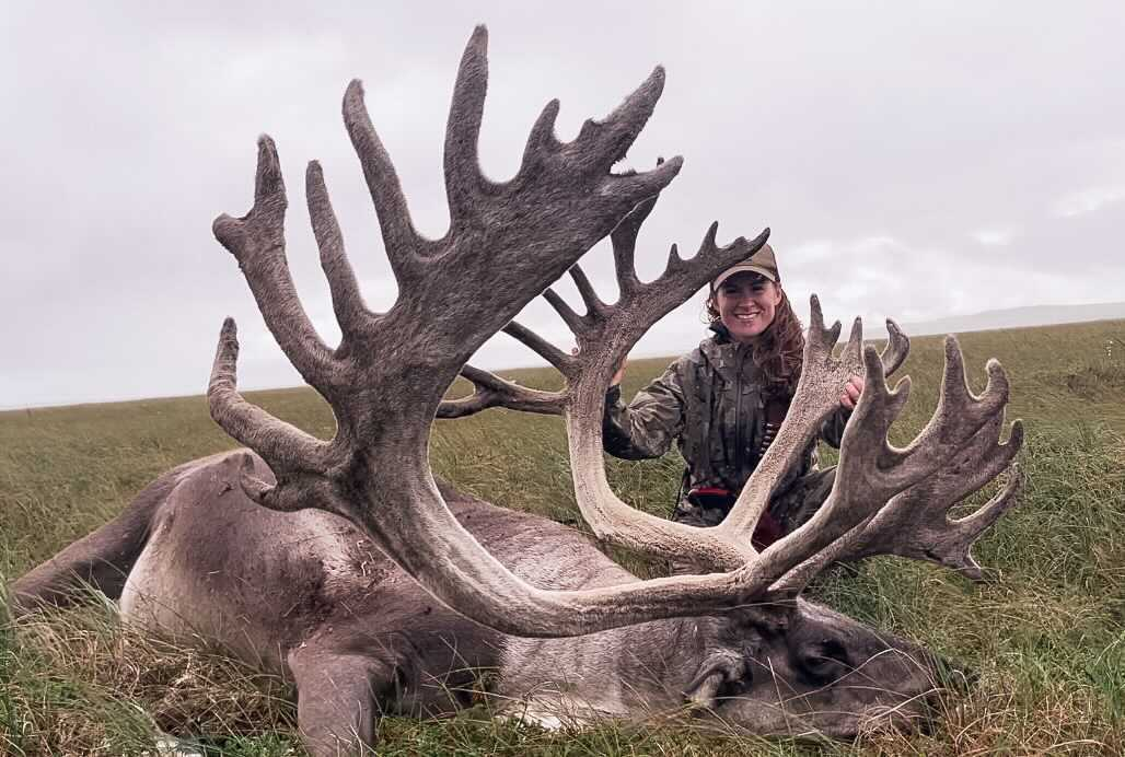 A woman stands behind the massive antlers of a dead caribou