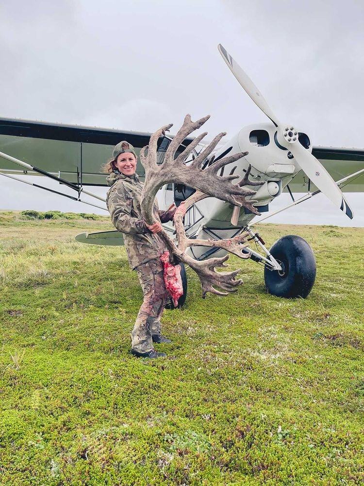Woman stands in front of propeller plan with caribou antlers