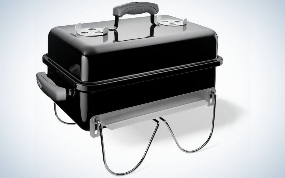 A large portable grill in the shape of a wide black and rectangular suitcase.